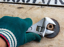 Hand holds wrench and tighten the nut on the wooden. Floor Royalty Free Stock Image