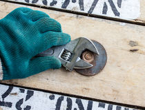 Hand holds wrench and tighten the nut on the wooden. Floor Stock Images