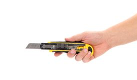 Hand holds yellow stationery knife Stock Photo