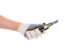 Hand holds yellow stationery knife. Royalty Free Stock Images