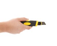 Hand holds yellow stationery knife. Royalty Free Stock Photo