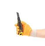Hand holds yellow stationery knife. Royalty Free Stock Photos