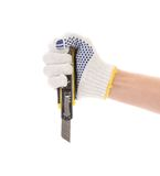 Hand holds yellow stationery knife. Royalty Free Stock Image