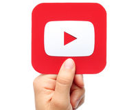 Hand holds YouTube icon. Kiev, Ukraine - August 18, 2015:Hand holds YouTube icon printed on paper on white background. YouTube is a video-sharing website Stock Image