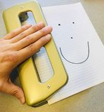 Hand hole punching a stack of paper at the office stock images