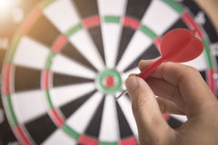 Hand holhing red arrow target center of dartboard. Concept business goal to marketing success Stock Photo