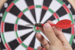 Hand holhing red arrow target center of dartboard. Concept business goal to marketing success Royalty Free Stock Photography