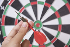 Hand holhing red arrow target center of dartboard. Concept business goal to marketing success Royalty Free Stock Images