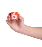 Hand holind colorful plastic numbers on white background Stock Image