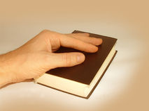 Hand on Holy Bible. Male hand on Holy Bible stock images