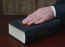 Hand on the holy book - Bible Royalty Free Stock Image