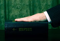 Hand on the holy book - Bible Stock Image