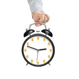 Hand hooking alarm clock with money face Stock Photography