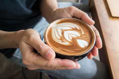 Hand on hot coffee latte Royalty Free Stock Photos