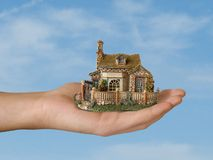 Hand with house. On sky background Royalty Free Stock Photo