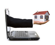 Hand with a house. Exiting from a laptop Stock Images