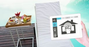 Hand with house application on digital tablet with lounge chair and breakfast in background Stock Images