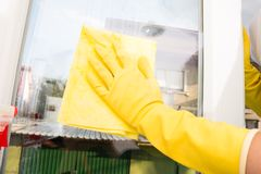 Hand of housewife cleaning and washing the window. With spray Royalty Free Stock Photos