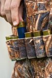 Hand of hunter pulling cartridge from the bandoleer Stock Photos
