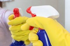 Hand i den gula gummihandsken som rymmer en blå rengörande sprejflaska klar att göra ren en spegel Tvätta, göra ren och torka beg royaltyfri foto