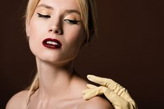 hand i den gula handsken som trycker på den sinnliga nakna blonda flickan arkivbild