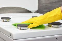 Hand i den vita ugnen för gul handskelokalvård med den gröna trasan Arkivfoton