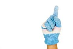 Hand i gesten nummer ett för blåttvinterhandske mot vit backg Royaltyfri Bild