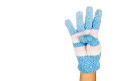 Hand i gesten nummer fyra för blåttvinterhandske mot vitbaksida Royaltyfria Foton