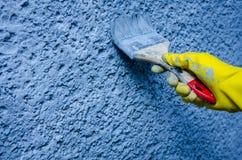 Hand i gul handskemålning på väggen Arkivfoto