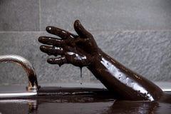 Hand i gyttjebadet för avslappnande och sunt royaltyfria bilder