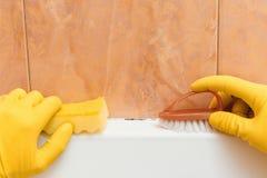 Hand i handskar som jag önskar att göra ren formen i badrummet royaltyfria foton