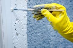 Hand i handske med en målarfärgborste Royaltyfri Foto