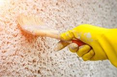 Hand i handske med en målning för målarfärgborste på väggen Arkivbild