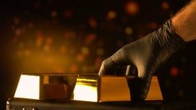 Hand i handsken som sätter guld- guldtacka, utvärdering av ädelmetaller, pantbank lager videofilmer