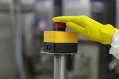 Hand i handsken som trycker på knappen Royaltyfri Fotografi