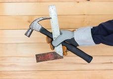 Hand i linjal och hammare för handskeinnehavjärn royaltyfri fotografi
