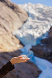 Hand with ice and Briksdal glacier - Norway Stock Image