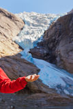 Hand with ice and Briksdal glacier - Norway Royalty Free Stock Image