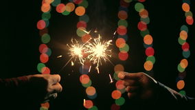 Hand ignites a sparkler from another stock video