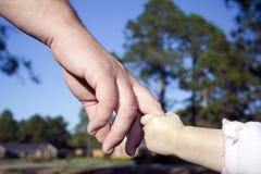 Hand ihres Vaters des Mädchens Holding Lizenzfreies Stockfoto