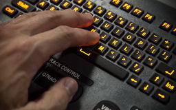 Hand on illuminated industrial qwerty keyboard. Selective focus royalty free stock photos