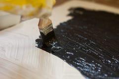 Hand im gelben Handschuh malt eine schwarze Oberfläche mit weißem Stein Lizenzfreies Stockfoto