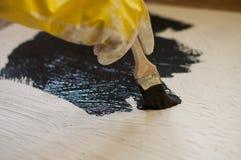 Hand im gelben Handschuh malt eine schwarze Oberfläche mit weißem Stein Lizenzfreie Stockfotos