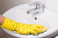 Hand im gelben Handschuh mit Schwammreinigungswanne Lizenzfreies Stockbild