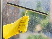 Hand im gelben Handschuh wäscht Fenster durch Gummiwalze Lizenzfreies Stockbild