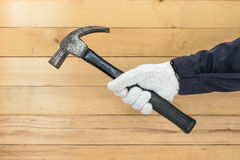 Hand im Handschuh, der Hammer hält Stockfoto