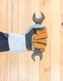 Hand im Handschuh, der Hammer hält Stockfotos