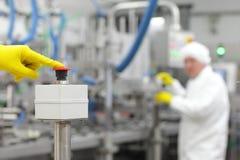 Hand im Handschuh, der Knopf - Beginnen des industriellen Prozesses drückt Stockfoto