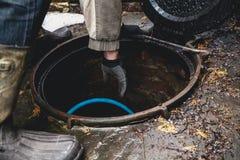 Hand im Handschuh fällt in Abwasserkanal Stockfotos