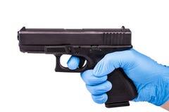 Hand im Handschuh hält Pistole Lizenzfreie Stockbilder